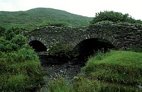 River by stone arched bridge with hill in the background