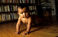 A baby crawling on a wooden floor