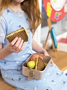 Girl holding lunch box, close-up