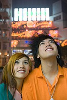 Teenage couple looking up, lights in background