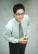 Businessman standing, holding cup of tea, smiling at camera, high angle view