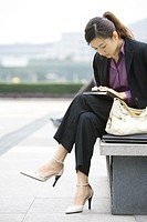 Young businesswoman sitting on bench looking down at cell phone