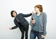 Young woman holding cell phone, looking over shoulder at male friend dancing behind her