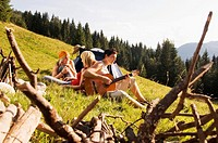 Three young people having picnic, man playing guitar
