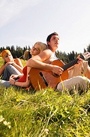 Young people in meadow, man playing guitar, low angle view