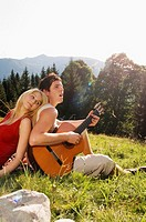 Young couple sitting in meadow, man playing guitar