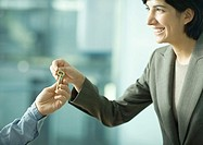 Professional woman handing man set of keys