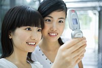 Two young female friends looking at cell phone together, close-up