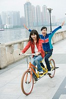 Two friends riding tandem bicycle