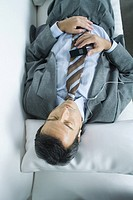 Businessman lying down, listening to earphones