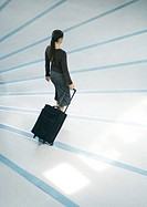 Woman walking with suitcase, full length, high angle view