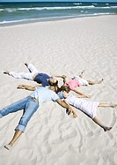 Family lying on sand, heads together and arms and legs out