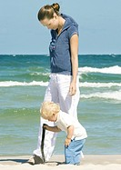 Young woman walking on beach next to toddler