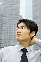 Businessman with hand on back of neck, looking up and frowning
