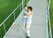 Couple on walkway, man spinning woman around in his arms