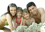 Family playing in sand at beach, smiling at camera, portrait