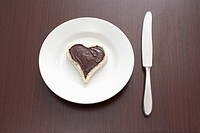 still life of sandwich with spread cut out in shape of heart on plate