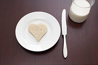 still life of bread cut out in shape of heart on plate and glass of milk