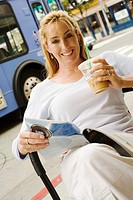 Woman drinking iced coffee, smiling, portrait