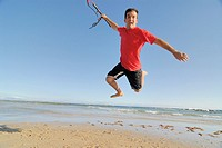 Male kite surfer jumping on beach