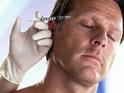 Mature man recieving injection in forehead