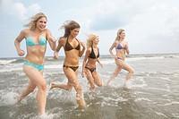 Four teenage girls 16-17 running into sea