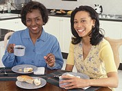 Two women having breakfast, portrait, smiling