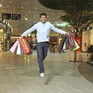 Man with shopping bags in mall, jumping, smiling, portrait
