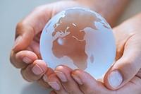 Human hand holding globe, close-up