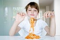 Close-up of a boy eating spaghetti