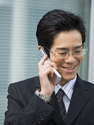 Smiling businessman, using a cellular phone in the office