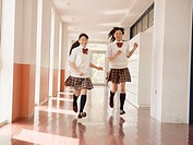 Two schoolgirls running in corridor
