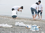 Pairs of sneakers on the beach