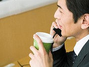 Calling businessman holding a cup of coffee