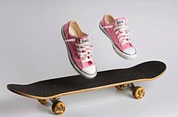 Pink shoes land on a skateboard