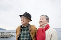 Senior couple looking up at the seaside, front view