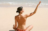 Rear view of a woman exercising on a beach