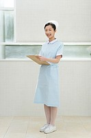 Portrait of a nurse holding a clipboard, smiling and looking at camera, front view
