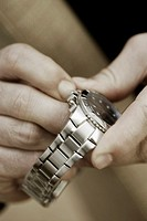 Close-up of a person's hand holding a wristwatch