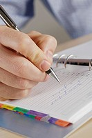 Close-up of a person's hand writing on a spiral notebook