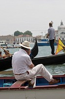 Rear view of a man sitting in a gondola, and using a mobile phone, Venice, Veneto, Italy