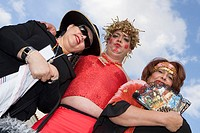 Low angle view of a mature man with two mature women wearing costumes