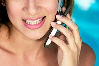 Close-up of a young woman using a mobile phone and smiling