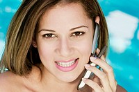 Portrait of a young woman using a mobile phone and smiling (thumbnail)