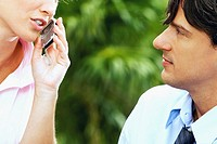 Close-up of a businesswoman talking on a mobile phone and a businessman looking at her