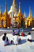 Rear view of pilgrims praying in front of a pagoda, Shwedagon Pagoda, Yangon, Myanmar (thumbnail)