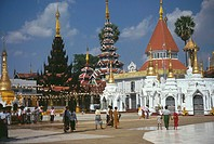 Pilgrims walking in front of a pagoda, Shwedagon Pagoda, Yangon, Myanmar