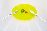 Close-up of a fork and a knife with a cherry tomato on a plate