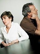 Close-up of a mature couple sitting back to back