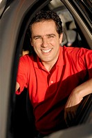 Portrait of a young man sitting in a car and smiling